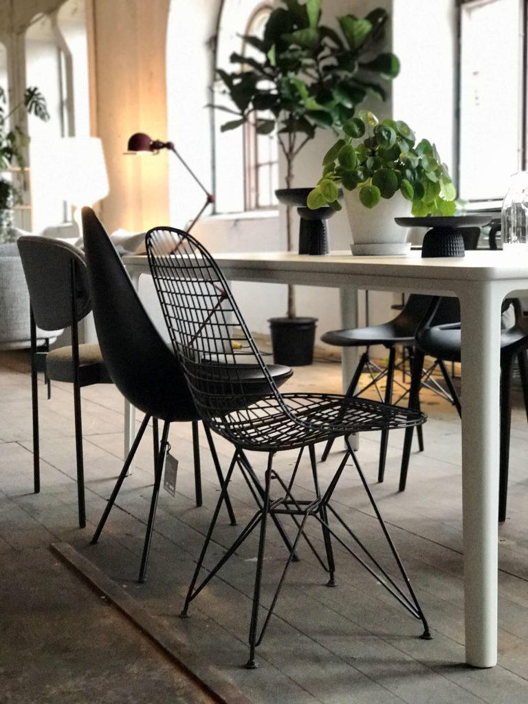 Svarta stolar i olika former runt matbord