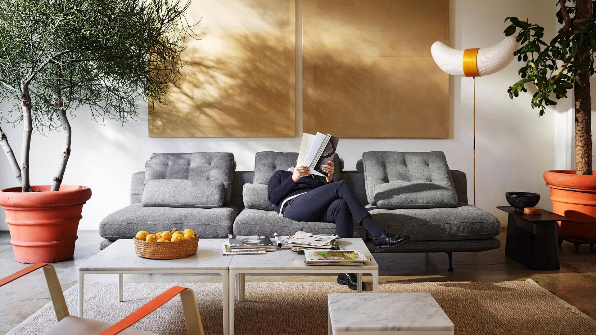 Person sitter i grå soffa och läser magasin